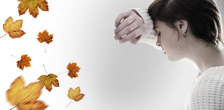 desolaci�n: Sad pretty brunette leaning against wall against autumn leaves pattern Foto de archivo