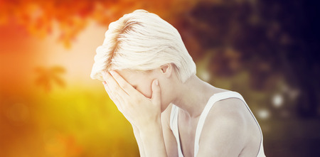 desolaci�n: Sad blonde woman crying with head on hands  against autumn scene