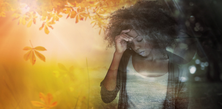 Sad woman holding her forehead with her hand against autumn scene 스톡 콘텐츠