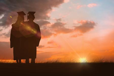 capelli lunghi: Due studenti in veste di laurea spalla a spalla contro il cielo arancione e blu con nuvole