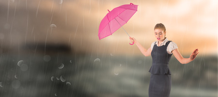 stormy sea: Pretty redhead businesswoman holding umbrella against stormy sea with lighthouse Stock Photo