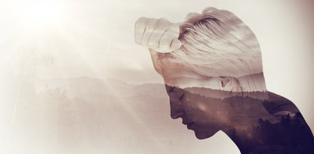 dreariness: Sad blonde woman with her head on wall  against trees and mountain range against cloudy sky