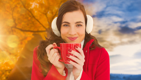 changing clothes: Woman in winter clothes enjoying a hot drink against autumn changing to winter Stock Photo