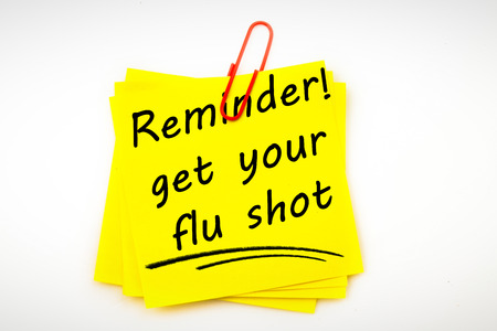 Flu shot reminder against sticky note with red paperclip Stok Fotoğraf