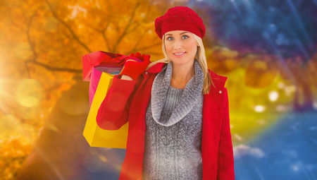 changing clothes: Blonde in winter clothes holding shopping bags against autumn changing to winter Stock Photo