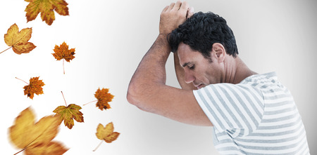 desolación: Upset man leaning on white background against autumn leaves pattern