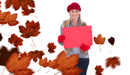 rood teken: Blonde in winter clothes holding red sign against autumn leaves Stockfoto