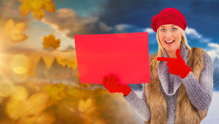 changing clothes: Blonde in winter clothes holding red sign against autumn changing to winter Stock Photo