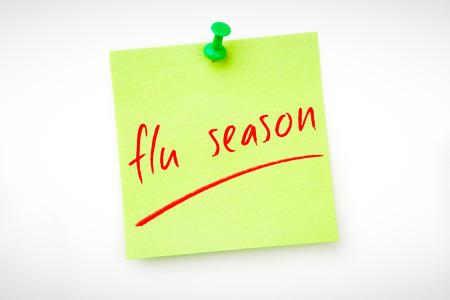flu vaccination: flu season against green pinned adhesive note