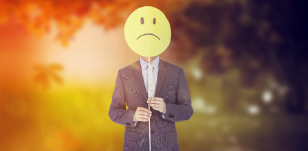 sad smiley: Businessman holding sad smiley in front of face against autumn scene