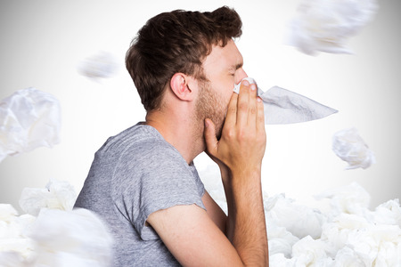blowing nose: Close up side view of man blowing nose against white background with vignette