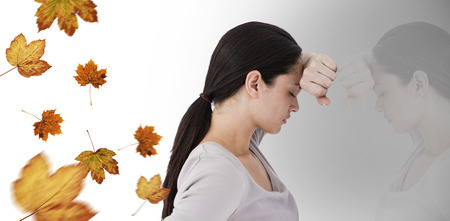 wistfulness: Sad woman leaning against the wall against autumn leaves pattern