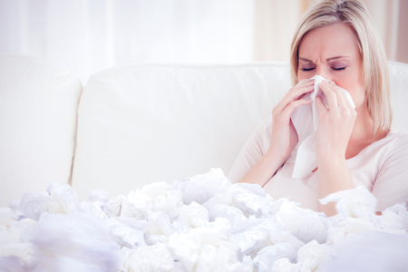woman blowing: Woman blowing her nose against used tissues