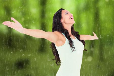 raining: Morena despreocupada con los brazos en contra de los árboles en el bosque otoñal