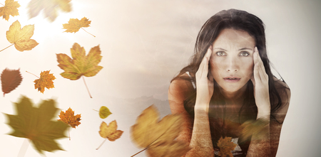 Portrait of upset woman with headache against autumn leaves