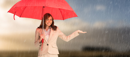 lady in red: Happy businesswoman holding umbrella against cloudy sky