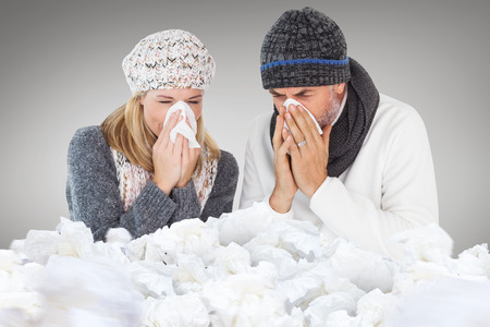 cold background: Couple sneezing in tissue against grey vignette