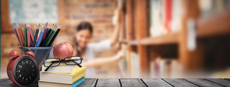 Schulbedarf auf dem Schreibtisch gegen Lehrer und kleine Mädchen Auswählen Buch in der Bibliothek