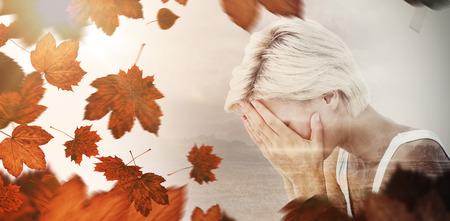 femme blonde: Sad femme blonde pleure avec la tête sur les mains contre les feuilles d'automne Banque d'images