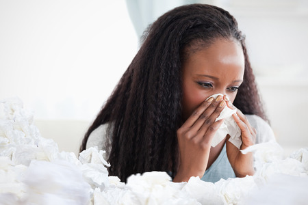 cold woman: Close up of woman blowing her nose against used tissues Stock Photo