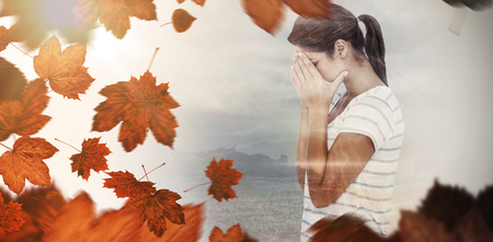 desolaci�n: Side view of upset woman covering face against autumn leaves