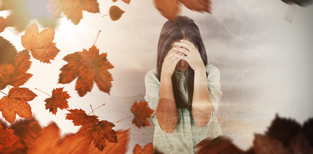 apprehensive: Troubled woman crying against autumn leaves Stock Photo