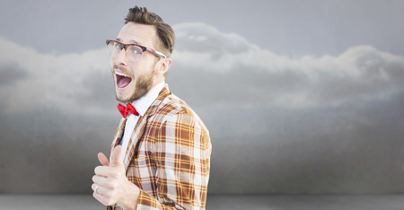 cheesy grin: Geeky hipster pointing at camera against clouds in a room