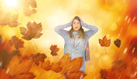 Anxious pretty brunette wearing winter clothes posing against orange abstract light spot design