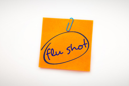 flu shots: flu shots against orange adhesive note with a paperclip