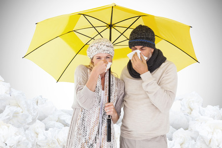 realtionship: Couple sneezing in tissue while standing under umbrella against white background with vignette Stock Photo