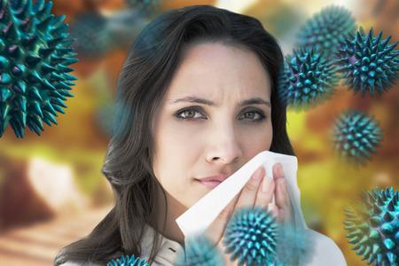 Morena con un resfriado contra la escena del otoño
