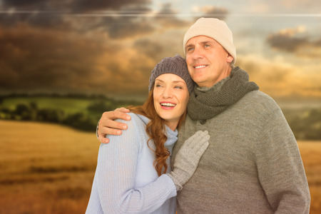 warm clothing: Couple in warm clothing embracing against country scene
