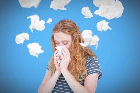 nariz: Mujer rubia enferma que sopla su nariz contra el fondo azul con la ilustración Foto de archivo