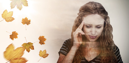 pounding head: Blonde woman having headache against autumn leaves pattern