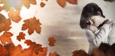 wistfulness: Sad pretty brunette thinking with arms crossed against autumn leaves Stock Photo