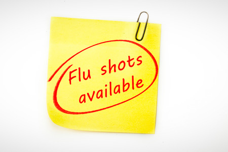 flu vaccines: flu shots available against  sticky note with grey paperclip Stock Photo