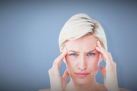 pounding head: Pretty blonde suffering from headache looking at camera  against blue background Stock Photo