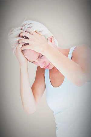 pounding head: Sad blonde woman with head pain holding her head  against grey background with vignette Stock Photo