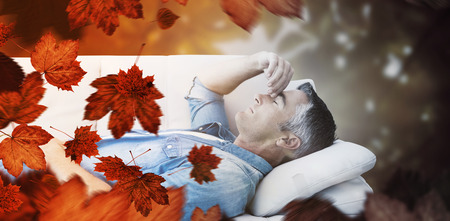 pounding head: Man suffering from headache while on sofa against autumn scene