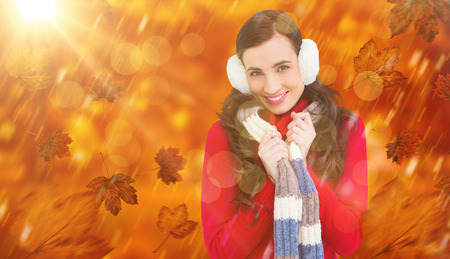 ear muffs: Happy brunette in winter clothes smiling at camera  against park