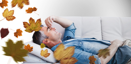 wincing: Man suffering from headache while on sofa against autumn leaves Stock Photo