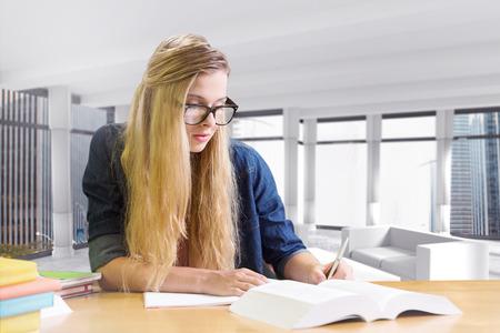 estudiando: Estudiante que estudia en la biblioteca contra la sala de vistas de la ciudad moderna