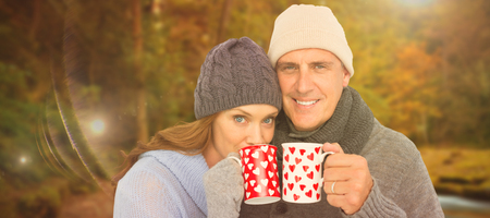 warm clothing: Happy couple in warm clothing holding mugs against autumn scene