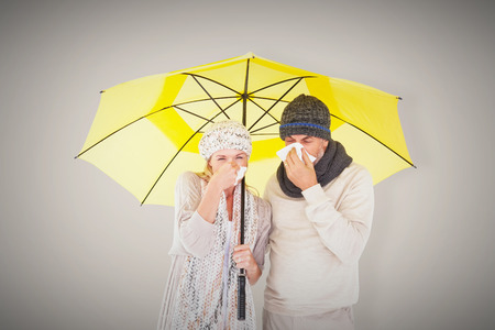 realtionship: Couple sneezing in tissue while standing under umbrella against grey background with vignette