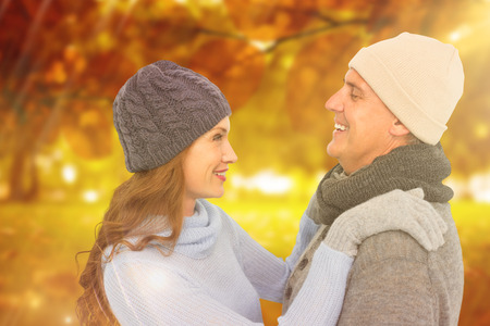 warm clothing: Happy couple in warm clothing against autumn scene