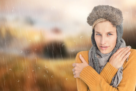 shivering: Woman in winter clothes shivering over white background against country scene Stock Photo