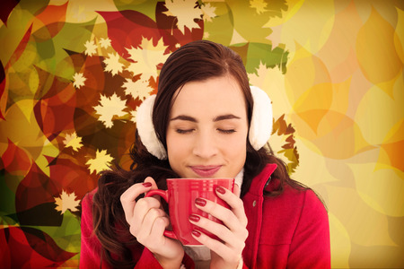 ear muffs: Woman in winter clothes enjoying a hot drink eyes closed against autumnal leaf pattern Stock Photo