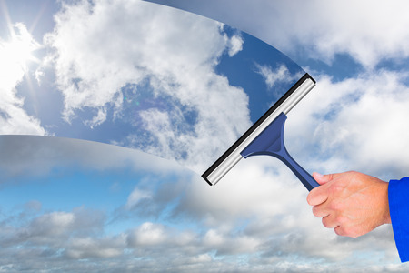 boiler suit: Hand using wiper against blue sky with clouds