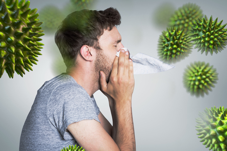 blowing nose: Close up side view of man blowing nose against grey vignette Stock Photo