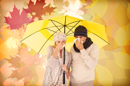 realtionship: Couple sneezing in tissue while standing under umbrella against autumnal leaf pattern